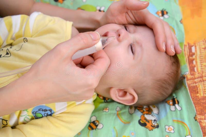 妇女从鼻子删除软泥给有一台鼻吸气器的病的哭泣的婴孩 免版税库存照片