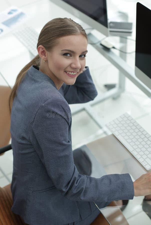 妇女货币管理人坐他的工作场所 免版税库存图片