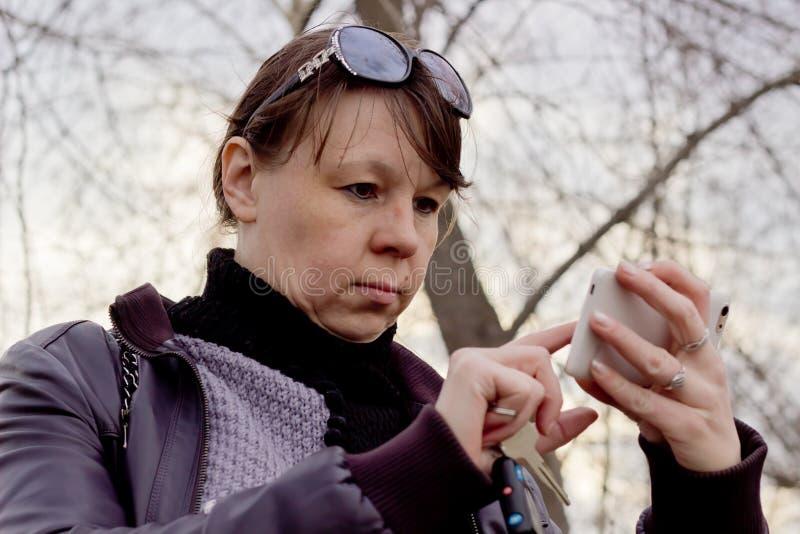 妇女从您的智能手机的检查消息 库存照片