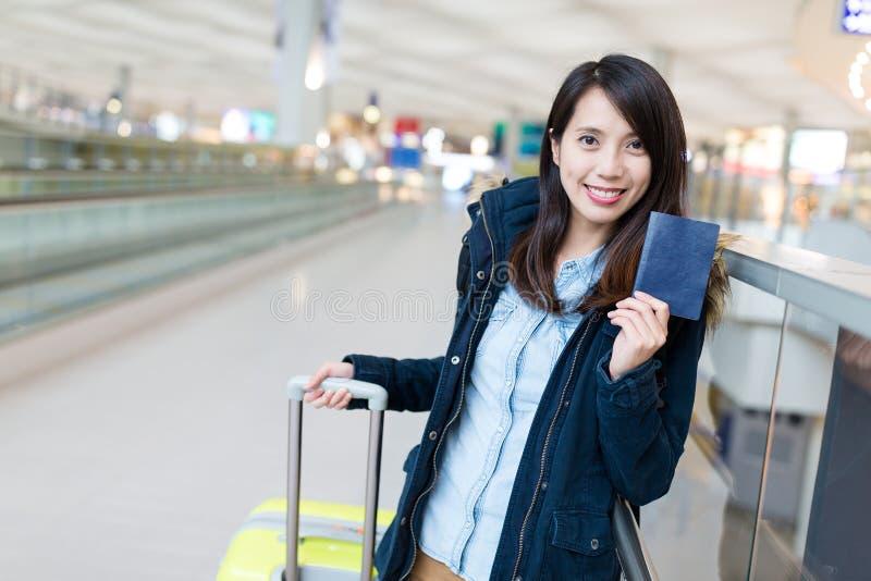 妇女去旅行带着她的手提箱和持护照 免版税库存照片