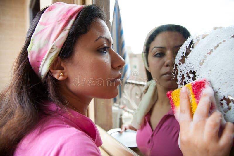 妇女洗涤一个镜子窗口 库存图片