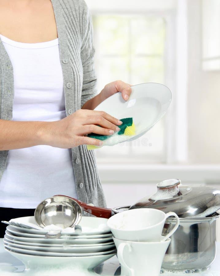 妇女洗涤的盘在厨房里 图库摄影