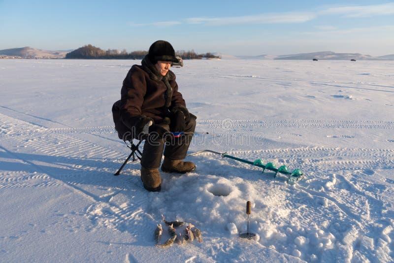妇女-渔夫从孔的抓住鱼在海岛的背景的一个大冻湖 免版税库存照片