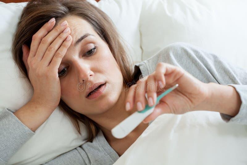 妇女以热病在床上 免版税库存照片