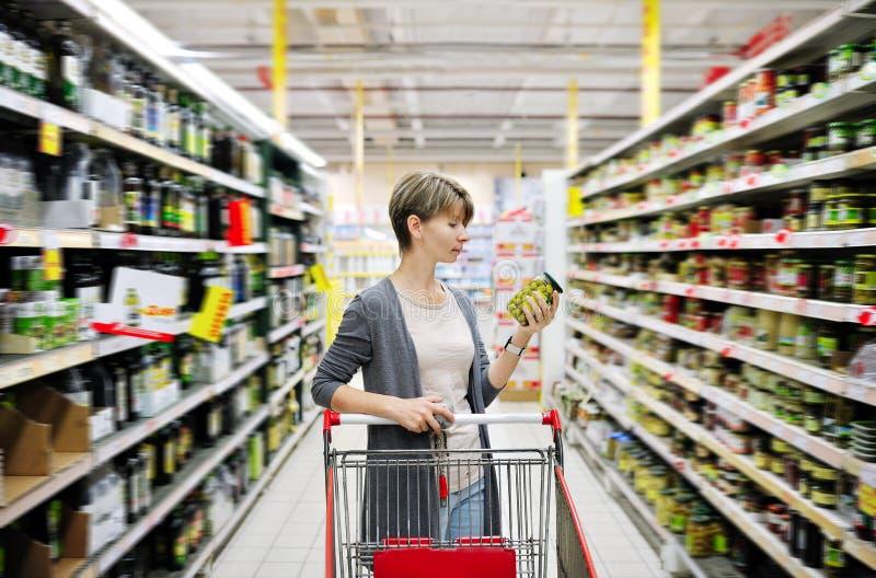 妇女购物和选择物品在超级市场 免版税库存照片