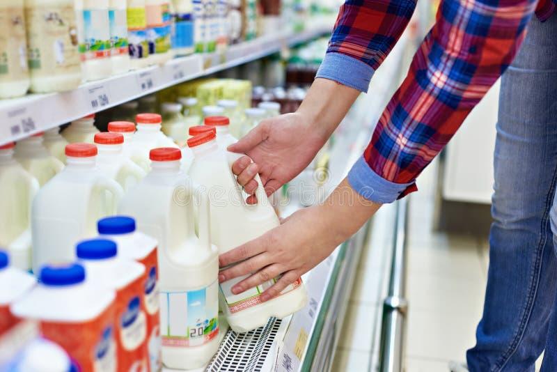 妇女购物牛奶在商店 库存图片