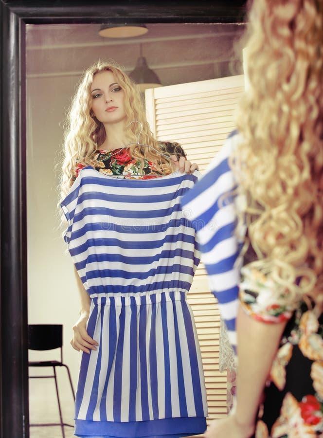 妇女看在镜子的购物礼服 免版税库存图片