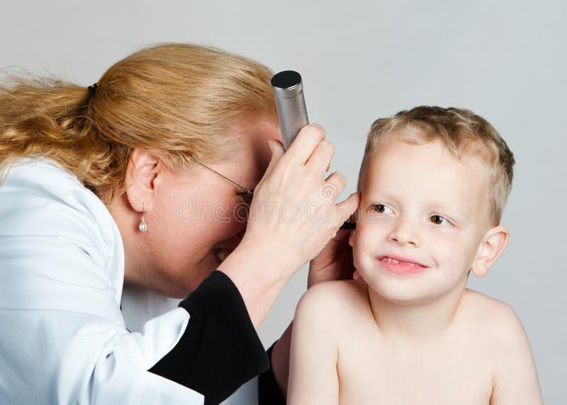 妇女医生审查的儿童的耳朵 免版税库存照片