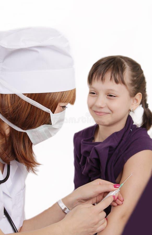 妇女医生接种的女孩在手中 库存图片