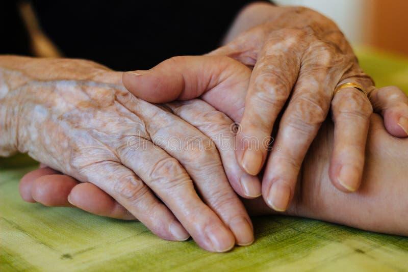 妇女给祖母她的手 免版税库存图片