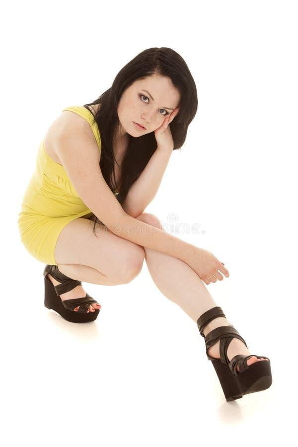 妇女黄色短的礼服坐神色 免版税库存照片
