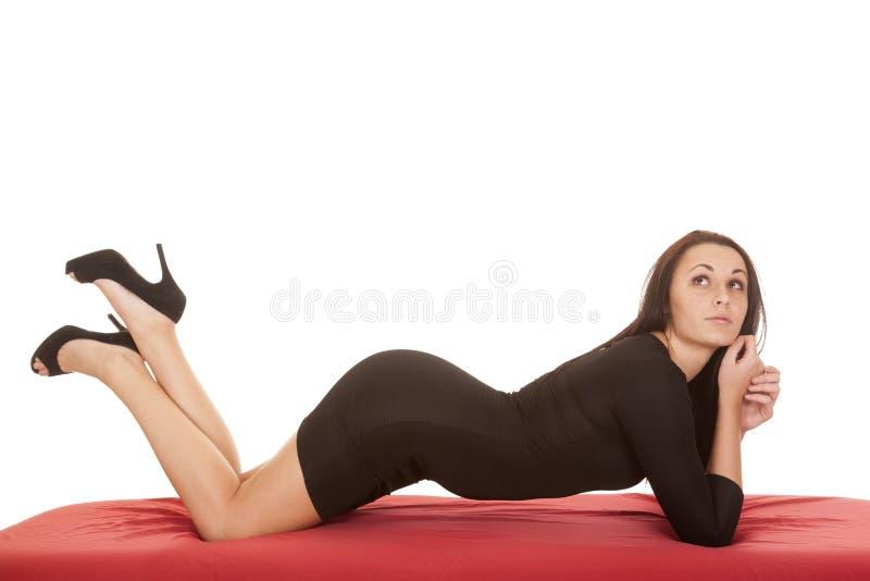 妇女黑色礼服放置前面查寻红色板料。 库存图片
