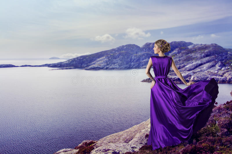 妇女紫色礼服,看山海,海岸的典雅的女孩 免版税图库摄影