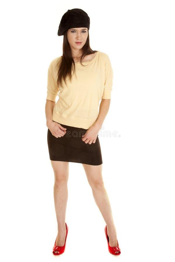 妇女黄色衬衣黑帽会议红色鞋子站立 免版税库存图片