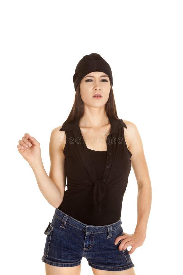 妇女黑衬衣和帽子一手严肃 免版税库存照片