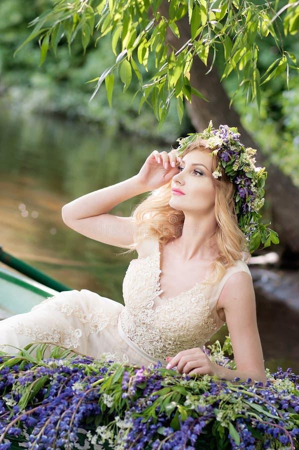 妇女画象有坐在有花的小船的花圈的 夏天 免版税库存照片