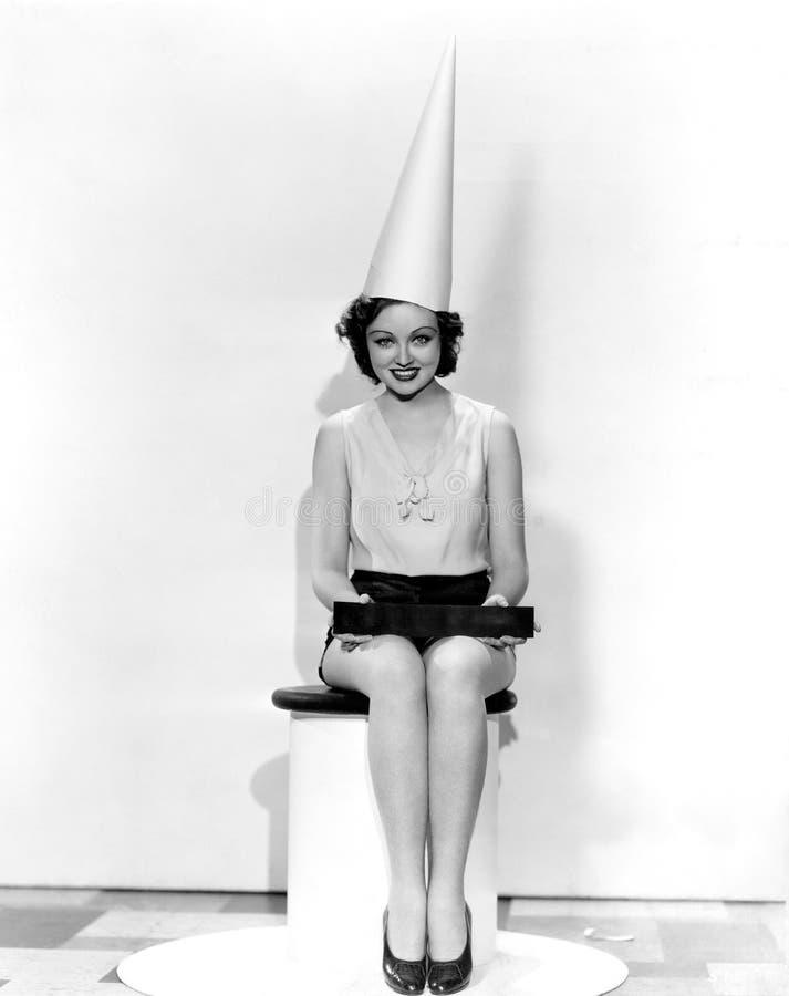 妇女画象有愚人标志佩带的圆锥形纸帽的(所有人被描述不更长生存,并且庄园不存在 Suppli 免版税库存照片