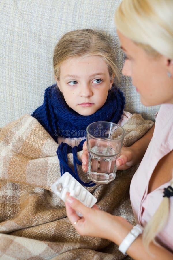 妇女画象有有的抗生素和的孩子的流感 免版税库存照片