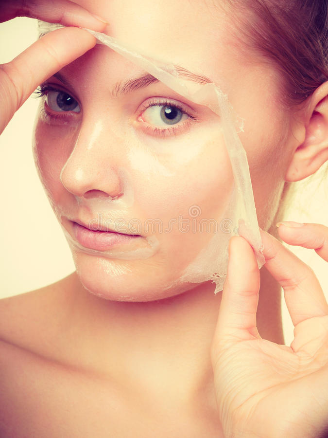 妇女去除面部剥落面具 免版税图库摄影