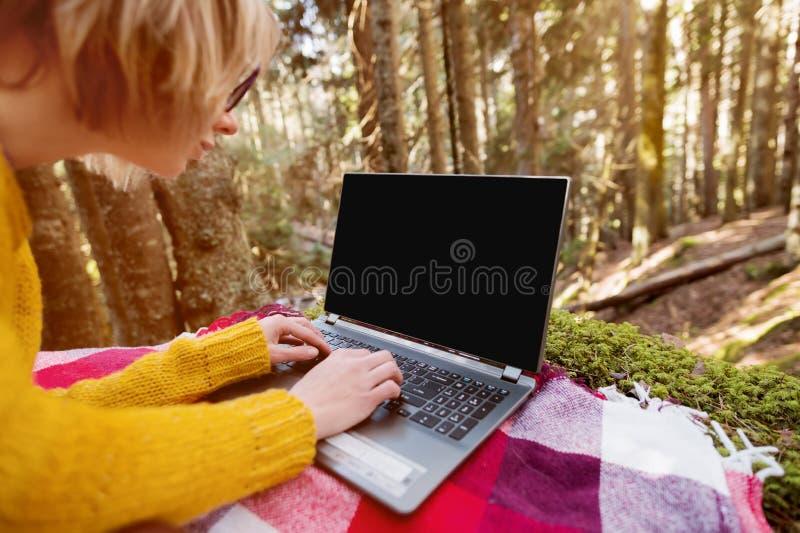 妇女` s手的大模型图象使用和输入在有一个空白的黑桌面的一台膝上型计算机在说谎格子花呢披肩的草 免版税库存照片