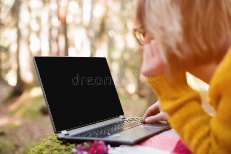 妇女` s手的大模型图象使用和输入在有一个空白的黑桌面的一台膝上型计算机在说谎格子花呢披肩的草 免版税库存图片