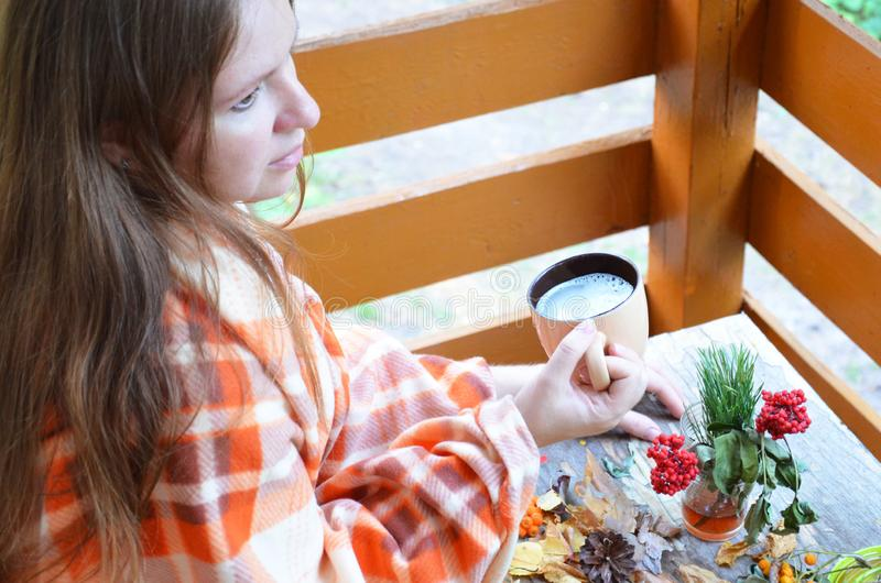 妇女` s手拿着一个杯子热的饮料、秋天、秋天叶子、热的通入蒸汽的咖啡和在木桌上的一条温暖的围巾 免版税库存图片