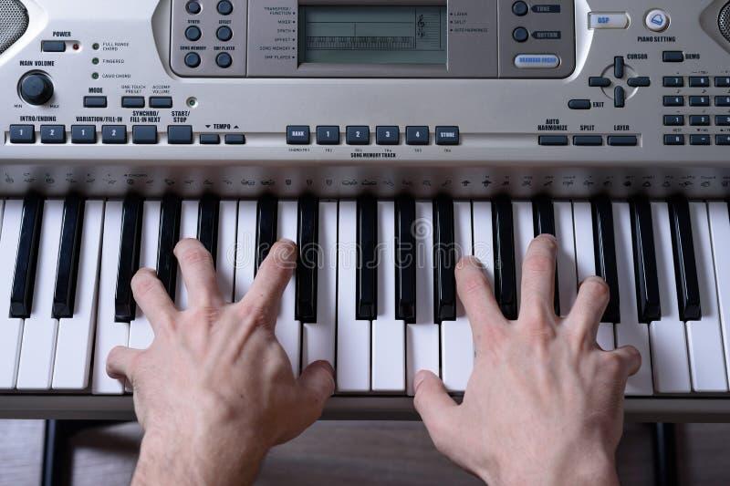 妇女` s前面背面图递播放电子钢琴的钥匙 库存照片