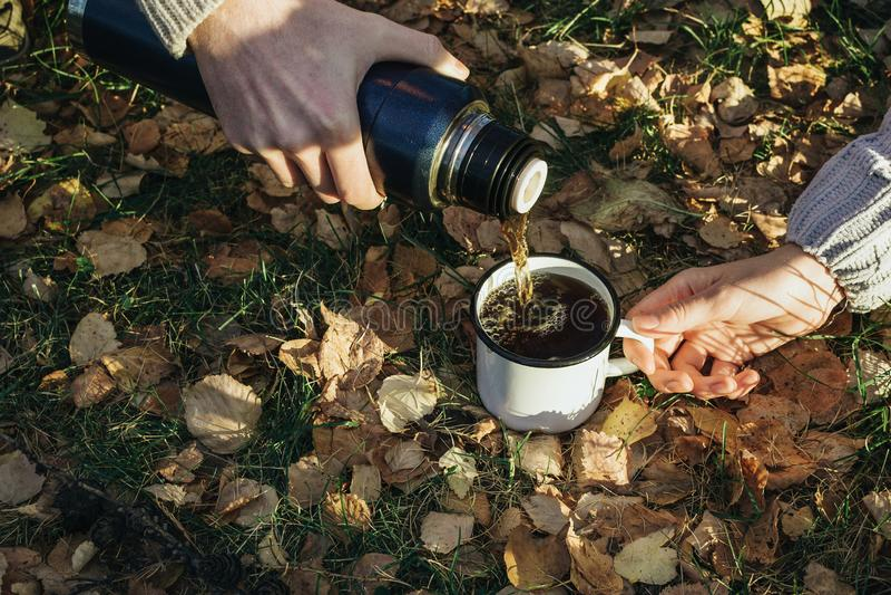 妇女` s和人` s特写镜头在森林递拿着金属杯子和热水瓶和倒茶户外 免版税库存照片