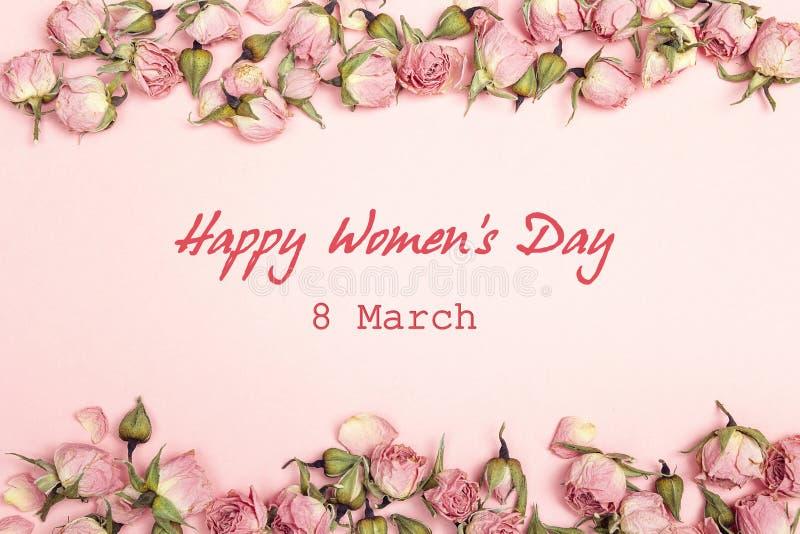 妇女` s天与小干燥玫瑰的问候消息在桃红色backgr 库存图片