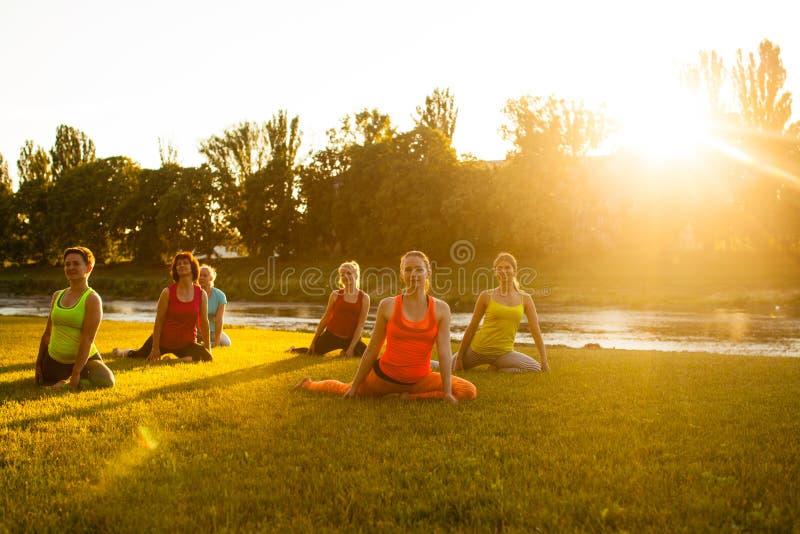 妇女` s室外瑜伽训练 免版税图库摄影