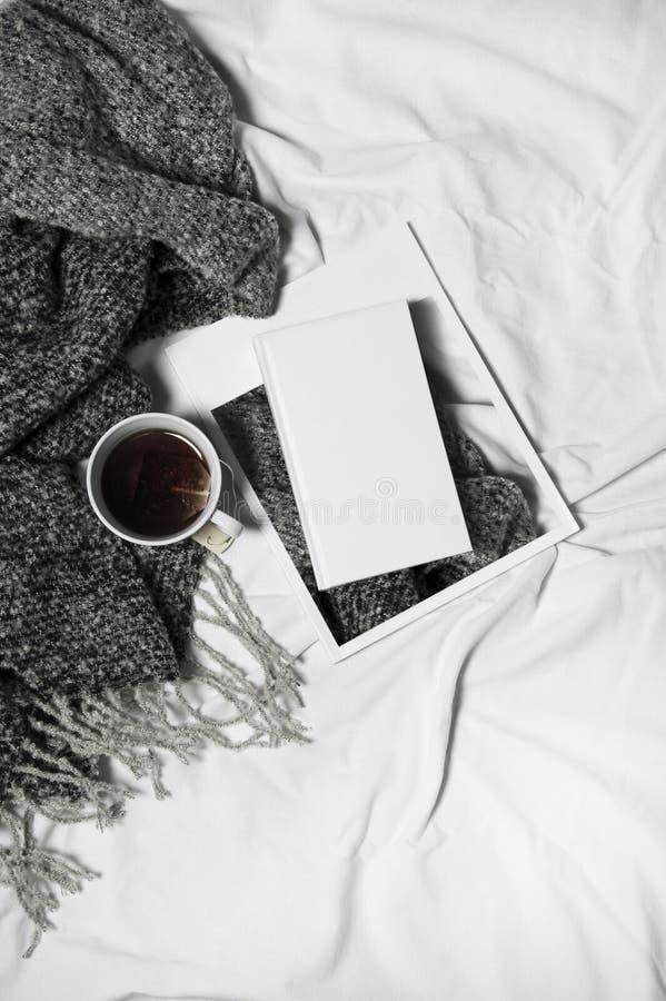 妇女` s床顶视图在冷气候的一懒惰星期日早晨 与书、咖啡和温暖的衣裳的生活方式 库存照片