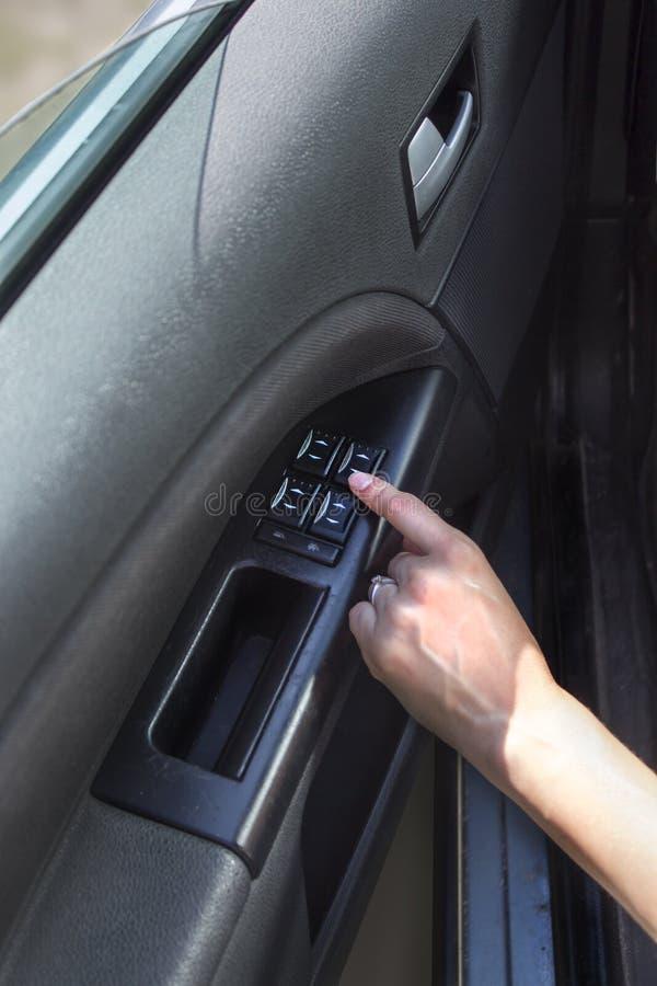 妇女` s手接触在汽车的窗口调整按钮 免版税库存图片