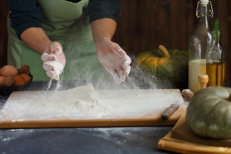 妇女` s手揉面团 在木桌上的烘烤成份 免版税库存照片