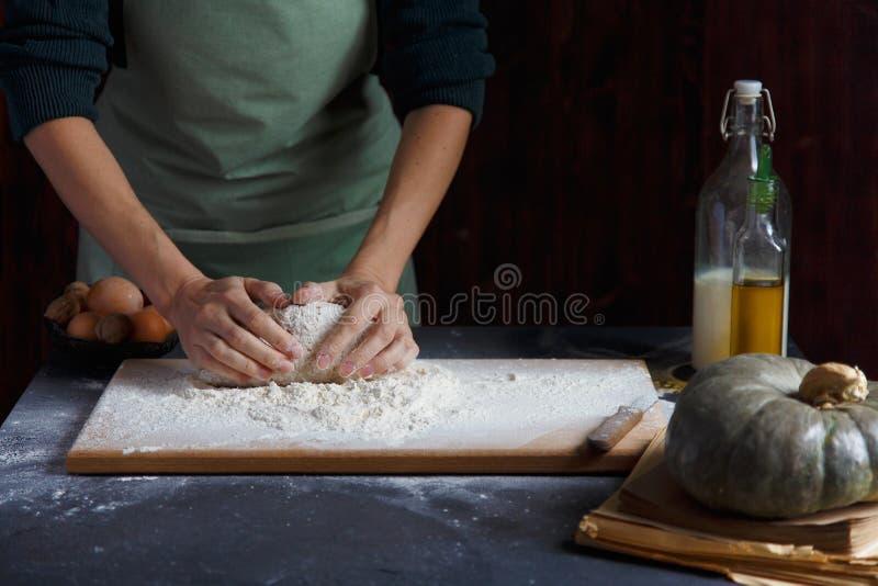 妇女` s手揉面团 在木桌上的烘烤成份 免版税库存图片