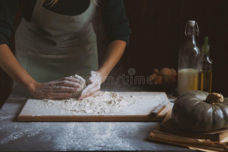 妇女` s手揉面团 在木桌上的烘烤成份 库存照片