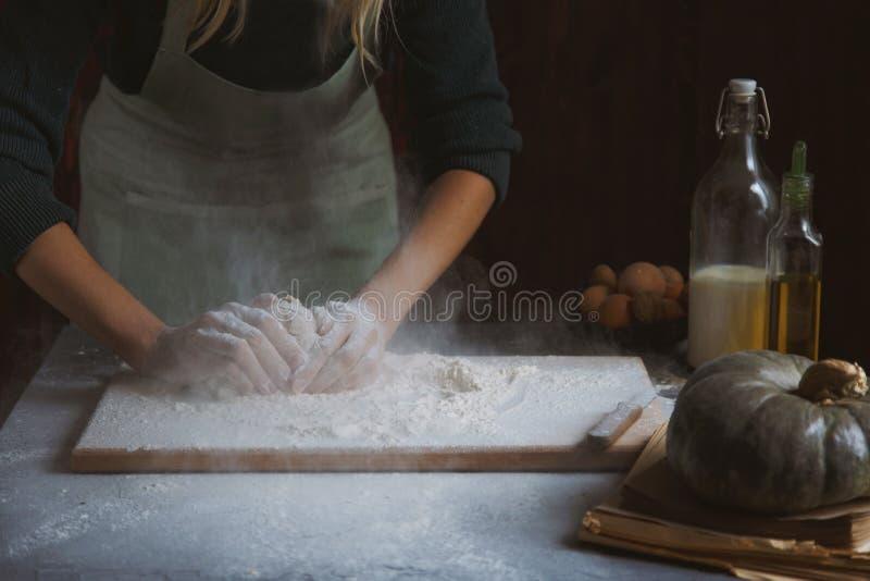 妇女` s手揉面团 在木桌上的烘烤成份 免版税图库摄影
