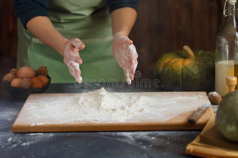 妇女` s手揉面团 在木桌南瓜牛奶油面粉的烘烤的成份 免版税库存图片