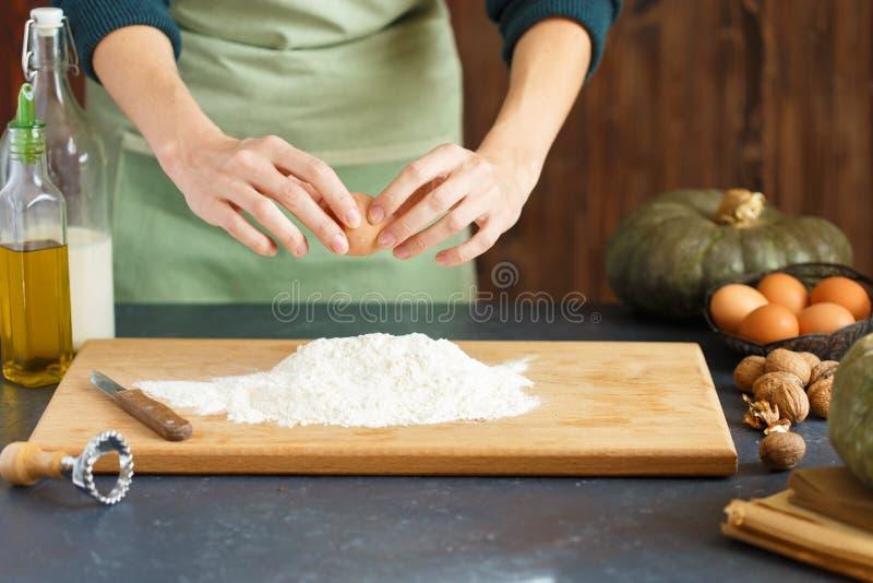 妇女` s手揉面团 糖果商驾驶鸡蛋入面粉 在木桌上烘烤 免版税库存图片