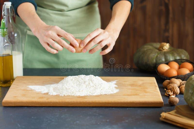 妇女` s手揉面团 糖果商驾驶鸡蛋入面粉 在木桌上烘烤 库存照片