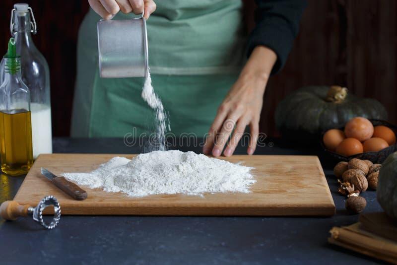 妇女` s手揉面团 糖果商驾驶鸡蛋入面粉 在木桌上烘烤 图库摄影