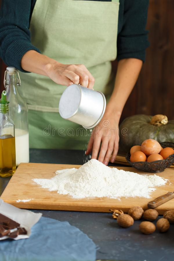 妇女` s手揉面团 糖果商驾驶鸡蛋入面粉 在木桌上烘烤 免版税库存照片