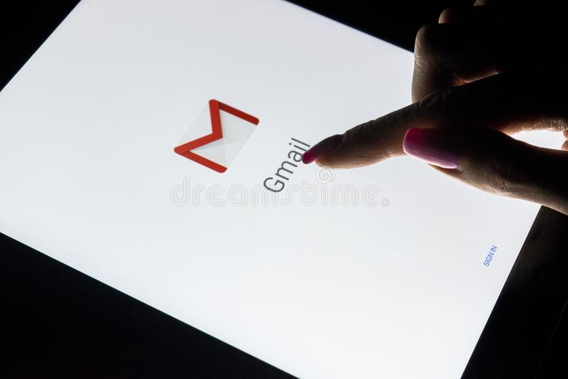 妇女` s手是在片剂计算机iPad的触摸屏赞成在与开放谷歌Gmail应用的晚上 Gmail是自由电子邮件 免版税图库摄影