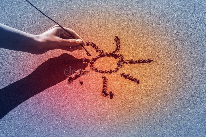 妇女` s手由海,焕发作用画在沙子的太阳 免版税库存图片