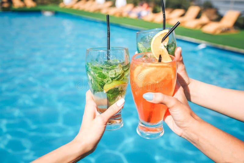 妇女` s手的图片拿着三杯在水池前面的鸡尾酒 有两绿色和一橙味饮料 免版税库存照片