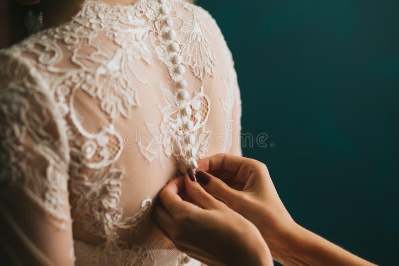 妇女` s手紧固与按钮在一个美丽的白色婚礼鞋带葡萄酒礼服特写镜头,早晨训练背面 turquo 库存照片