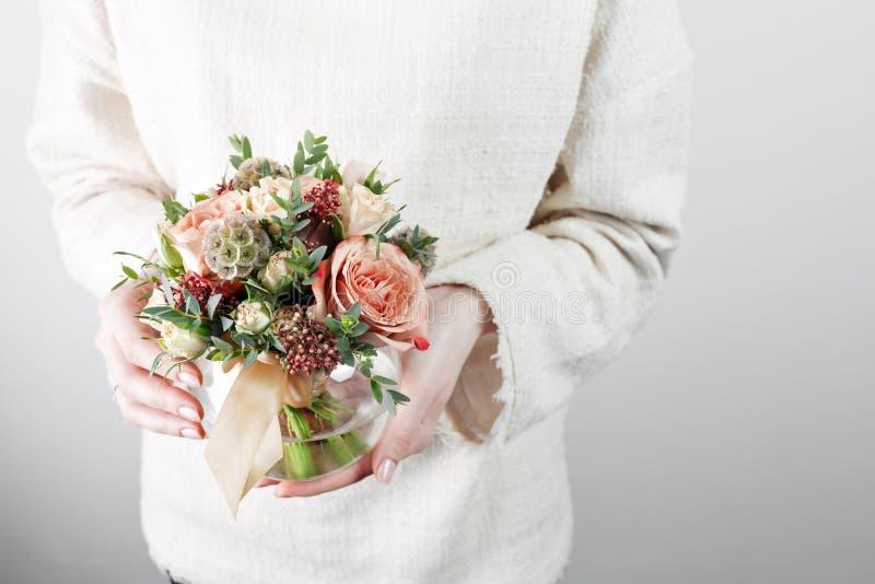 妇女` s手,拿着有森林春天花花束的玻璃花瓶,关闭 库存照片