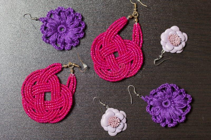 妇女` s服装jewelery 手工制造一套的耳环 黑暗的表面上的谎言 在视图之上 库存图片