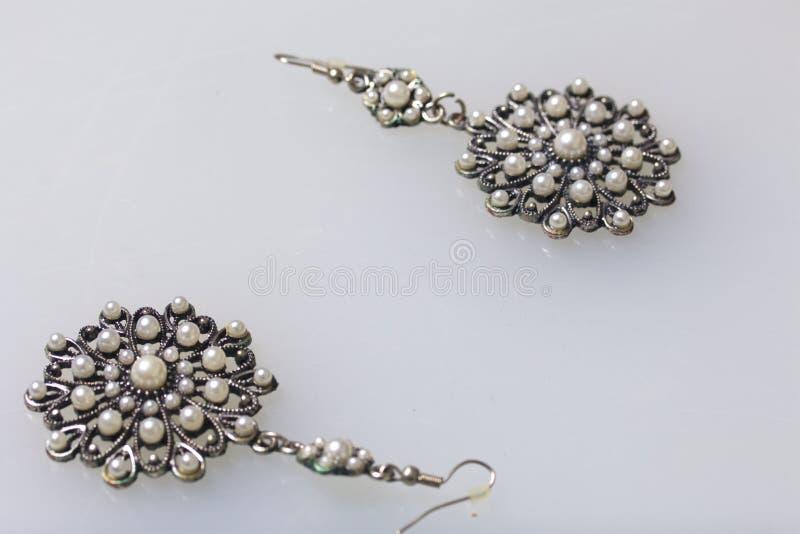 妇女` s服装jewelery 耳环由与石头的金属制成 白色表面上的谎言 在视图之上 图库摄影