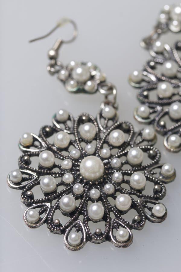 妇女` s服装jewelery 耳环由与石头的金属制成 白色表面上的谎言 在视图之上 库存照片