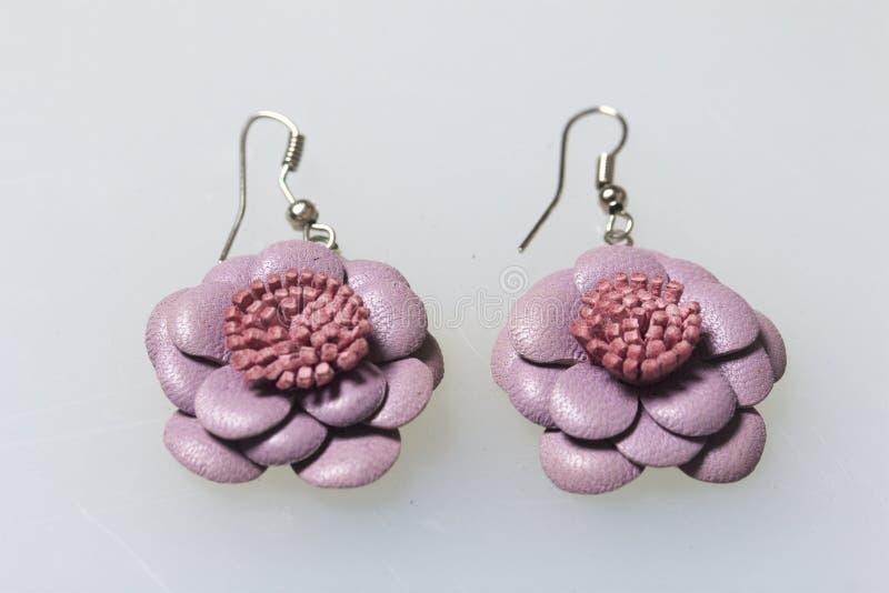 妇女` s服装jewelery 耳环由皮革制成,手工制造 白色表面上的谎言 在视图之上 库存照片